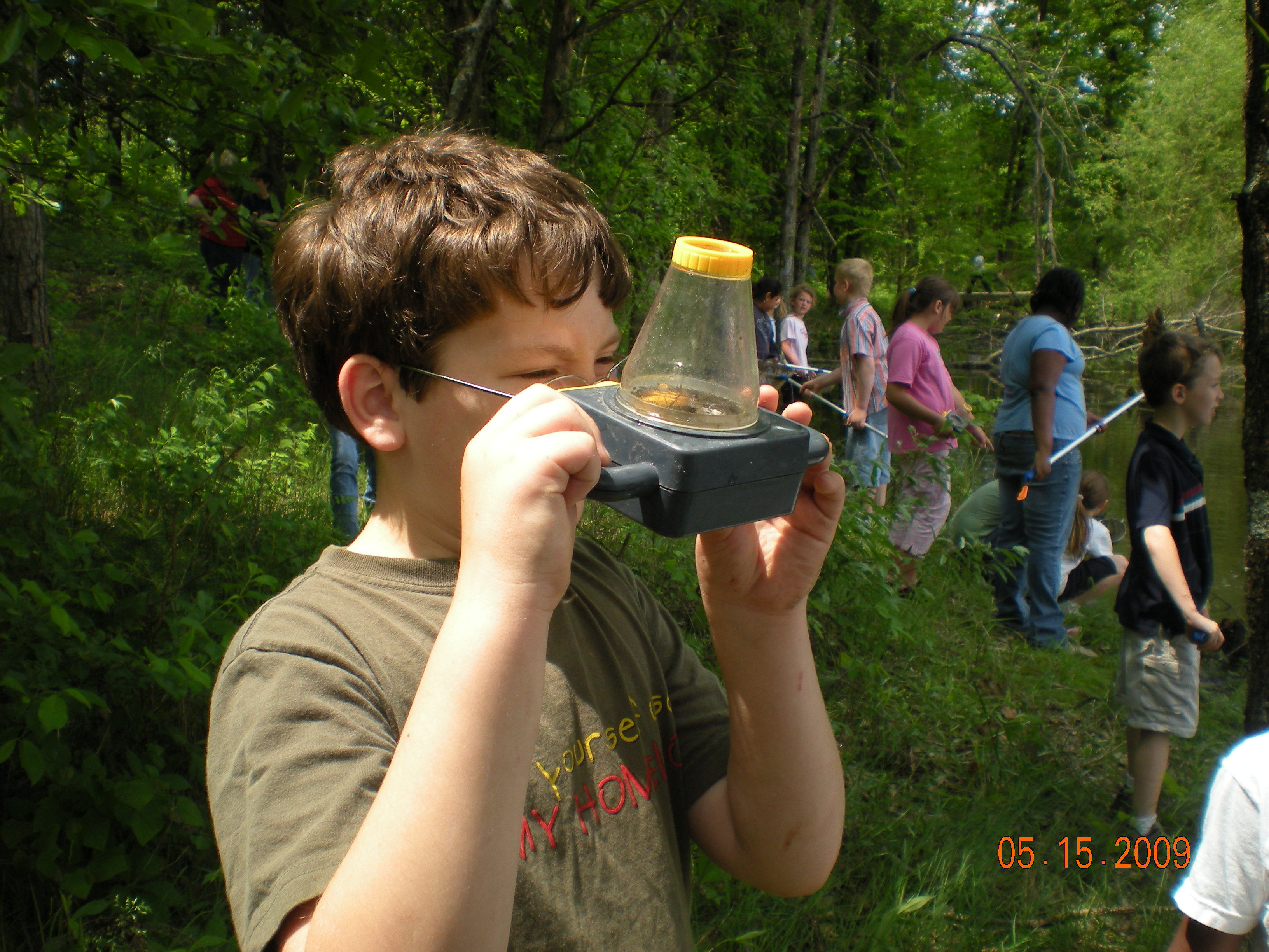 Hawthorne Elementary 3rd Grade student using an observation container to explore the pond